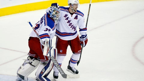 New York Rangers goalie Antti Raanta (32), from Finland, and New York Rangers center Derek Stepan (21) celebrate after an NHL hockey game against the Washington Capitals, Friday, March 4, 2016, in Washington. The Rangers won 3-2. (AP Photo/Alex Brandon)