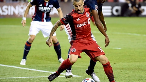 Toronto FC forward Sebastian Giovinco (10) tries to keep control of the ball under pressure from New England Revolution defender London Woodberry, right, during the second half of an MLS soccer match in Toronto on Friday, June 23, 2017. (Nathan Denette/The Canadian Press via AP)