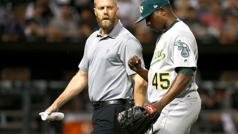 Oakland Athletics starter Jharel Cotton, right, leaves the game looking at his pitching thumb with a member of the medical staff during the sixth inning of a baseball game against the Chicago White Sox, Friday, June 23, 2017, in Chicago. (AP Photo/Charles Rex Arbogast)