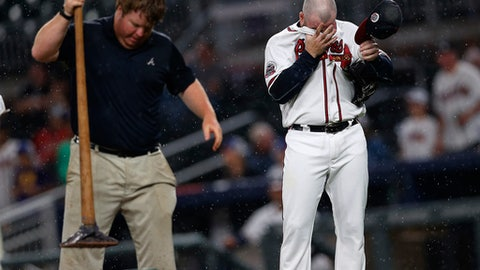 Atlanta Braves relief pitcher Jason Motte (30) dries his face as a member of the grounds crew works on the pitcher's mound during the sixth inning of the team's baseball game against the Milwaukee Brewers on Friday, June 23, 2017, in Atlanta. (AP Photo/John Bazemore)