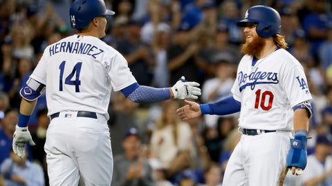 Los Angeles Dodgers' Justin Turner, right, celebrates after scoring on a double by Cody Bellinger with Enrique Hernandez during the second inning of a baseball game against the Colorado Rockies in Los Angeles, Friday, June 23, 2017. (AP Photo/Chris Carlson)