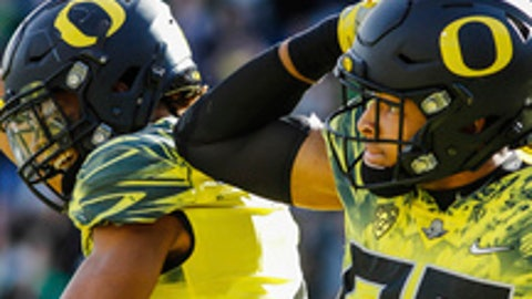 FILE - From top are photos showing Oregon NCAA college football players wearing green, black, and white helmets during NCAA college football games. The NCAA football oversight committee wants to determine whether style is coming at the expense of safety. The committee will meet next week in Indianapolis and one of the agenda items is to begin studying whether players using multiple helmets could increase the potential for concussions and serious head and neck injuries. (AP Photo/File)