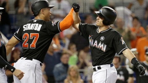 Miami Marlins' J.T. Realmuto, right, is met at the plate by Miami Marlins' Giancarlo Stanton (27) after hitting a three-run home run during the first inning of a baseball game against the Chicago Cubs, Saturday, June 24, 2017, in Miami. (AP Photo/Lynne Sladky)