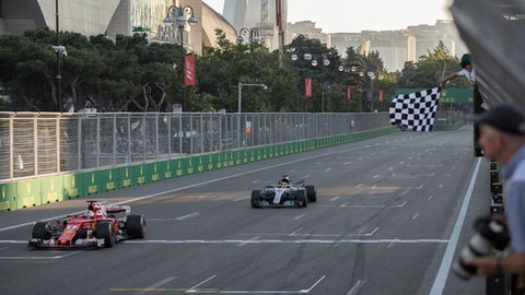 Ferrari driver Sebastian Vettel of Germany, left, and Mercedes driver Lewis Hamilton of Britain crosses the finish line at the Formula One Azerbaijan Grand Prix in Baku, Azerbaijan, Sunday, June 25, 2017. (Valdrin Xhemaj/Pool via AP)
