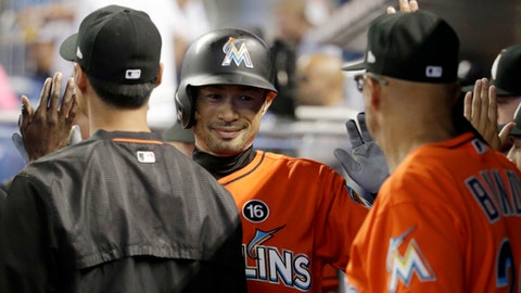 Miami Marlins' Ichiro Suzuki is congratulated in the dugout after scoring on a single hit by Marcell Ozuna during the first inning of a baseball game, Sunday, June 25, 2017, in Miami. (AP Photo/Lynne Sladky)
