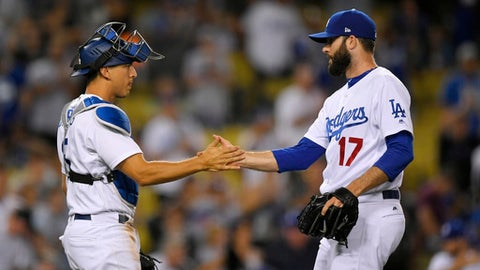 Los Angeles Dodgers catcher Austin Barnes, left, and relief pitcher Brandon Morrow congratulate each other after the Dodgers defeated the Los Angeles Angels 4-0 in a baseball game, Tuesday, June 27, 2017, in Los Angeles. (AP Photo/Mark J. Terrill)