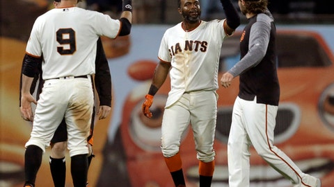 San Francisco Giants' Denard Span, center, celebrates with Brandon Belt (9) after hitting the game winning run single against the Colorado Rockies in the 14th inning of a baseball game Tuesday, June 27, 2017, in San Francisco. (AP Photo/Ben Margot)