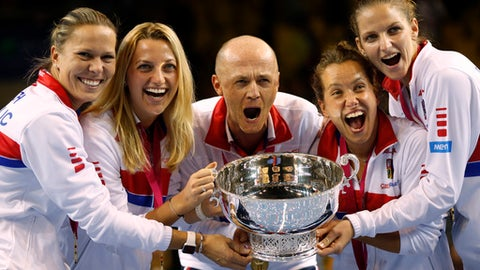 FILE - This is a Sunday, Nov. 13, 2016 file photo of the  Czech Republic team captain Petr Pala, center, and players hold the trophy after their victory against France, during the Fed Cup final in Strasbourg, eastern France.  The Davis Cup and Fed Cup are planning to combine forces into a World Cup of Tennis. A three-year deal starting in 2018 to combine the events was announced Wednesday June 28, 2017, by the International Tennis Federation. The changes still need to be approved at the federation's annual general meeting in August in Vietnam. (AP Photo/Jean-Francois Badias/File)