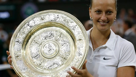 FILE - In this July 5, 2014, file photo, Petra Kvitova, of Czech Republic, holds the trophy after winning the women's singles final against Eugenie Bouchard at the All England Lawn Tennis Championships in Wimbledon, London. Kvitova still has not regained full strength in her left hand, the one she uses to swing a tennis racket _ and the one that was stabbed by an attacker at her home in December. The two-time Wimbledon champion is simply thrilled to be back on tour, and she's seen as a serious title contender on the grass on which she excels.(AP Photo/Sang Tan, File)