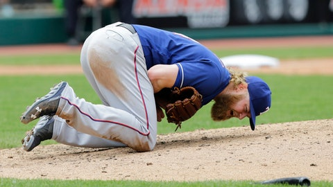 Texas Rangers starting pitcher Andrew Cashner reacts after getting hit by the broken bat, foreground right, of Cleveland Indians' Edwin Encarnacion in the sixth inning of a baseball game, Thursday, June 29, 2017, in Cleveland. Encarnacion was safe at first base. Michael Brantley scored on the play. (AP Photo/Tony Dejak)