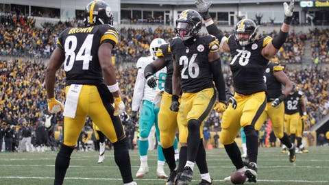Jan 8, 2017; Pittsburgh, PA, USA; Pittsburgh Steelers running back Le'Veon Bell (26) celebrates with wide receiver Antonio Brown (84) and tackle Alejandro Villanueva (78) after gaining yardage near the goal line against the Miami Dolphins during the second quarter in the AFC Wild Card playoff football game at Heinz Field. The Steelers won 30-12. Mandatory Credit: Charles LeClaire-USA TODAY Sports