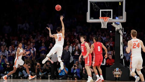 Florida guard Chris Chiozza (11) puts up a last second 3-point shot to score the game-winning points against Wisconsin in overtime of an East Regional semifinal game of the NCAA men's college basketball tournament, Saturday, March 25, 2017, in New York. Florida won 84-83. (AP Photo/Julio Cortez)