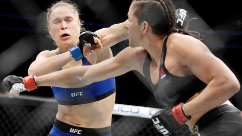 Amanda Nunes, right, throws a punch at Ronda Rousey in the first round of their women's bantamweight championship mixed martial arts bout at UFC 207, Friday, Dec. 30, 2016, in Las Vegas. Nunes won the fight after it was stopped in the first round. (AP Photo/John Locher)