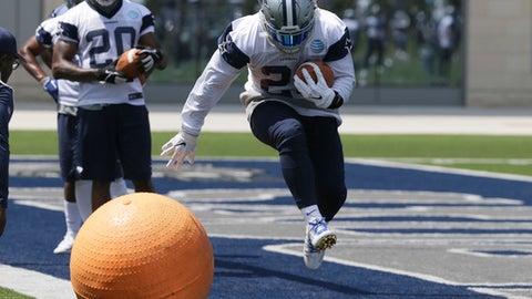 Dallas Cowboys running back Ezekiel Elliott (21) runs a drill as teammate Darren McFadden (20) looks on during an organized team activity at its NFL football training facility in Frisco, Texas, Wednesday, May 31, 2017. (AP Photo/LM Otero)