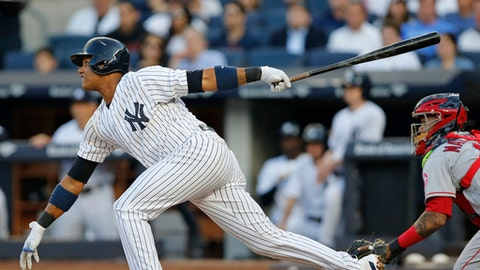 New York Yankees' Starlin Castro follows through on a first-inning RBI single in a baseball game against the Los Angeles Angels in New York, Thursday, June 22, 2017. Angels catcher Martin Maldonado is at right. (AP Photo/Kathy Willens)
