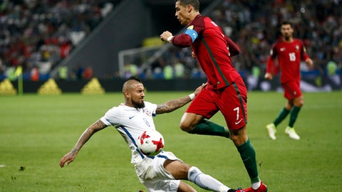 Chile's Arturo Vidal, left, tackles Portugal's Cristiano Ronaldo during the Confederations Cup, semifinal soccer match between Portugal and Chile, at the Kazan Arena, Russia, Wednesday, June 28, 2017. (AP Photo/Pavel Golovkin)