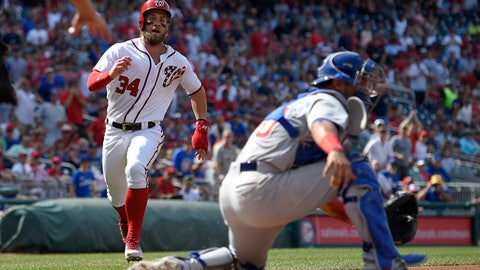 Washington Nationals' Bryce Harper runs towards home to score on a hit by Ryan Zimmerman AS Chicago Cubs catcher Willson Contreras, right, waits for the throw during the first inning of a baseball game, Thursday, June 29, 2017, in Washington. (AP Photo/Nick Wass)