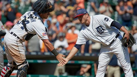 Detroit Tigers catcher James McCann (34) and relief pitcher Justin Wilson celebrate after their 7-4 win against the Cleveland Indians in the first baseball game of a doubleheader in Detroit, Saturday, July 1, 2017. (AP Photo/Rick Osentoski)
