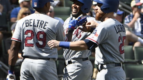 Texas Rangers' Elvis Andrus, center, is greeted by Adrian Beltre (29) and Jonathan Lucroy, right, after scoring against the Chicago White Sox during the eighth inning of a baseball game, Saturday, July 1, 2017, in Chicago. (AP Photo/David Banks)