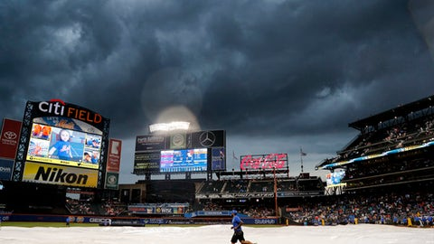 A member of the New York Mets grounds crew runs along the field after covering the field with a tarp during a rain delay of a baseball game against the Philadelphia Phillies, Saturday, July 1, 2017, in New York. (AP Photo/Julie Jacobson)