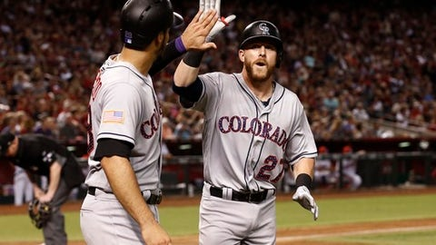 Colorado Rockies' Trevor Story (27) celebrates his two-run home run against the Arizona Diamondbacks with Nolan Arenado, left, during the seventh inning of a baseball game Saturday, July 1, 2017, in Phoenix. (AP Photo/Ross D. Franklin)