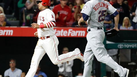 Los Angeles Angels' Yunel Escobar, left, scores past Seattle Mariners relief pitcher Marc Rzepczynski on a wild pitch during the seventh inning of a baseball game in Anaheim, Calif., Saturday, July 1, 2017. (AP Photo/Chris Carlson)