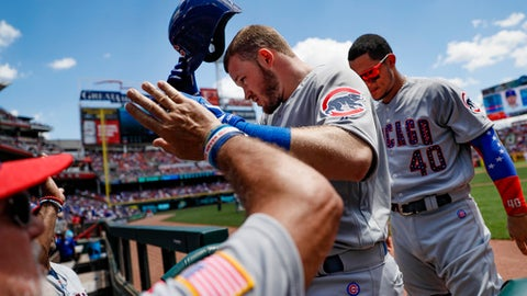 Chicago Cubs' Ian Happ, center, celebrates in the dugout after hitting a solo home run off Cincinnati Reds starting pitcher Tim Adleman in the fourth inning of a baseball game, Sunday, July 2, 2017, in Cincinnati. (AP Photo/John Minchillo)