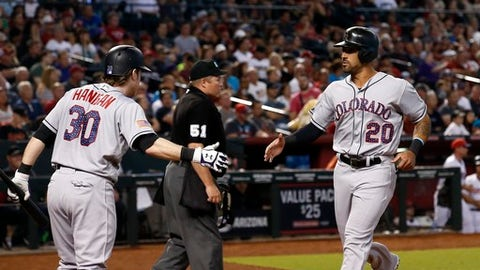 Colorado Rockies' Ian Desmond (20) celebrates his run against the Arizona Diamondbacks with Ryan Hanigan (30) as umpire Marvin Hudson (51) watches the infield during the fourth inning of a baseball game Sunday, July 2, 2017, in Phoenix. (AP Photo/Ross D. Franklin)