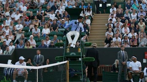 Jo—Wilfried Tsonga of France and Sam Querrey of the United States talk to the umpire about the match being called for lack of light, on day five at the Wimbledon Tennis Championships in London Friday, July 7, 2017. (AP Photo/Tim Ireland)