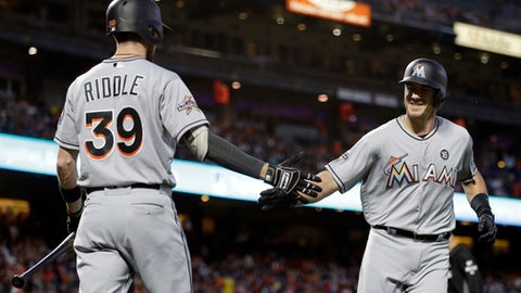 Miami Marlins' J.T. Realmuto, right, is congratulated by JT Riddle (39) after hitting a home run off San Francisco Giants' Cory Gearrin during the fifth inning of a baseball game Friday, July 7, 2017, in San Francisco. (AP Photo/Ben Margot)
