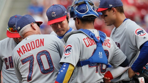 FILE - In this July 1, 2017, file photo, Chicago Cubs relief pitcher Koji Uehara, center left, meets with manager Joe Maddon (70) on the mound in the seventh inning of a baseball game against the Cincinnati Reds, in Cincinnati. The average time of a nine-inning game this season is a record 3 hours, 5 minutes, up from 3:00 last year and 2:56 in 2015. MLB is threatening to impose new pace rules for 2018, even if players don't agree.  (AP Photo/John Minchillo, File)