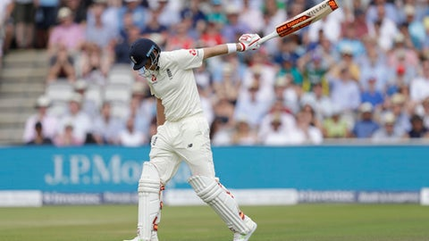 England captain Joe Root swings his bat in frustration as he walks off the field of play after losing his wicket from the bowling of South Africa's Keshav Maharaj during the first test between England and South Africa at Lord's cricket ground in London, Sunday, July 9, 2017. (AP Photo/Matt Dunham)