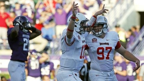 Illinois State kicker Sean Slattery (97) celebrates with quarterback Koty Thelen (17) after scoring the game-winning field goal as Northwestern running back Justin Jackson, left, reacts during the second half of an NCAA college football game in Evanston, Ill., Saturday, Sept. 10, 2016. Illinois State won 9-7. (AP Photo/Nam Y. Huh)