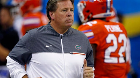 FILE - In this Dec. 3, 2016, file photo, Florida head coach Jim McElwain runs out on the field before the first half of the Southeastern Conference championship NCAA college football game against Alabama in Atlanta. The Southeastern Conference's Eastern Division will take center stage on Tuesday, July 11, 2017, at the league's annual media gathering. Florida, Georgia, Vanderbilt and Mississippi State are the four teams making the trek to SEC media days. (AP Photo/Butch Dill, File)
