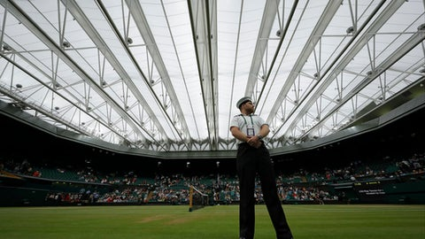 A member of the armed forces stands on Center Court after the roof was closed due to rain on day eight at the Wimbledon Tennis Championships in London Tuesday, July 11, 2017. (AP Photo/Alastair Grant)