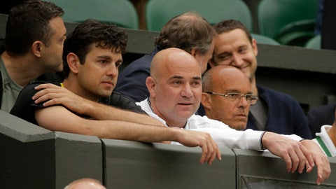 Mario Antic, left, and Andre Agassi, center, coaches of Serbia's Novak Djokovic take their seats before he plays his Men's Singles Match against Adrian Mannarino of France on day eight at the Wimbledon Tennis Championships in London Tuesday, July 11, 2017. (AP Photo/Alastair Grant)