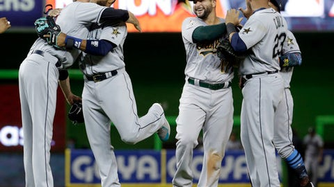 American League's Seattle Mariners Robinson Cano (22), second from left, is hugged by Cleveland Indians pitcher Andrew Miller, after winning the MLB baseball All-Star Game, Tuesday, July 11, 2017, in Miami. Cano hit a home run in the tenth inning to win the game. The American League defeated the National league 2-1. (AP Photo/Lynne Sladky)