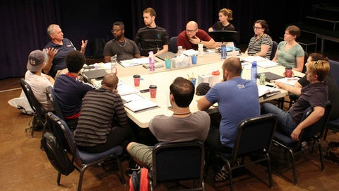 """Former UConn NCAA college basketball coach Jim Calhoun, rear left, gestures as he speaks to the cast and crew of the play """"Exposure"""" at the Eugene O'Neill Theater Center, Tuesday, July 11, 2017, in Waterford, Conn. Calhoun is serving as an adviser for the play about the darker side of college basketball recruiting. (AP Photo/Pat Eaton-Robb)"""