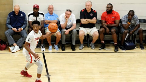 North Carolina head basketball coach Roy Williams and other basketball coaches watch a game during the opening night of the Nike Peach Jam at Riverview Park in North Augusta, S.C., Wednesday, July 12, 2017.  (AP Photo/Todd Bennett)