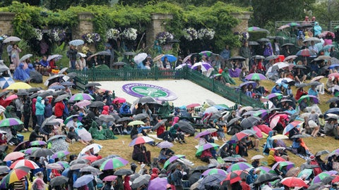 FILE - In this Tuesday, July 11, 2017 file photo spectators sitting on 'Murray Mound' shelter under umbrellas as they watch the Women's Quarterfinal Singles Match between Romania's Simona Halep and Britain's Johanna Konta on the big screen on day eight at the Wimbledon Tennis Championships in London. (AP Photo/Kirsty Wigglesworth, File)