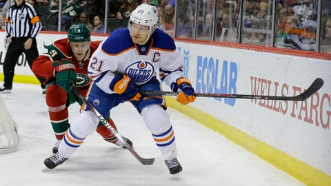 Edmonton Oilers defenseman Andrew Ference (21) controls the puck in front of Minnesota Wild center Mikko Koivu (9), of Finland, during the second period of an NHL hockey game in St. Paul, Minn., Tuesday, Feb. 24, 2015. (AP Photo/Ann Heisenfelt)