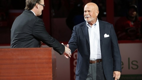 """FILE - In this Feb. 13, 2016, file photo, Carolina Hurricanes broadcaster John Forslund greets Hurricanes owner Peter Karmanos Jr., right, before the teams' NHL hockey game against the New York Islanders in Raleigh, N.C. Karmanos is considering an offer from someone who wants to purchase the team. Spokesman Mike Sundheim said in a statement attributed to the team that Karmanos """"also will continue to evaluate his other options, including retaining his ownership of the team."""" (AP Photo/Karl B DeBlaker, File)"""