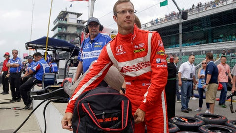 FILE - In this May 19, 2017, file photo, Sebastien Bourdais, of France, unpacks his helmet as he prepares to drive during a practice session for the Indianapolis 500 IndyCar auto race at Indianapolis Motor Speedway in Indianapolis. Bourdais is trading in his helmet for his smarts this weekend at the Honda Indy Toronto. The Frenchman is returning to the race track in a mentorship role for Dale Coyne Racing just two months after a crash during qualifying for the Indy 500. (AP Photo/Michael Conroy, File)