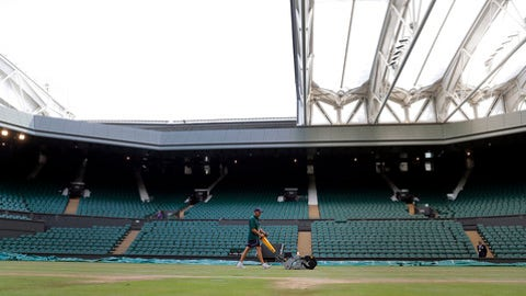 Rick Street mows the grass on Centre Court at the All England Club on day nine at the Wimbledon Tennis Championships in London Thursday, July 13, 2017. At 7:30 a.m. each day of the Wimbledon fortnight, hours before competition begins, the keepers of the grass gather to meticulously prepare the tournament's famous courts for play. (AP Photo/Alastair Grant)
