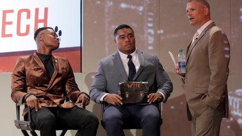 Virginia Tech head coach Justin Fuente, right, talks with players Cam Phillips, left, and Andrew Motuapuaka, of New Zealand, during the Atlantic Coast Conference NCAA college football media day in Charlotte, N.C., Friday, July 14, 2017. (AP Photo/Chuck Burton)