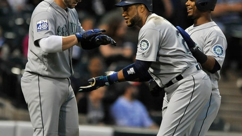 Seattle Mariners' Robinson Cano center, celebrates with teammates Jean Segura, right, and Nelson Cruz, left, at home plate after hitting a three-run home run during the third inning of a baseball game against the Chicago White Sox, Friday, July 14, 2017, in Chicago. (AP Photo/Paul Beaty)