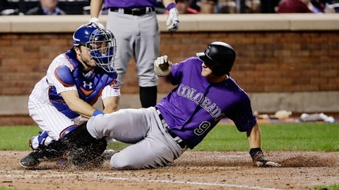 New York Mets catcher Travis d'Arnaud, left, tags out Colorado Rockies' DJ LeMahieu on a throw by left fielder Yoenis Cespedes during the sixth inning of a baseball game Friday, July 14, 2017, in New York. (AP Photo/Frank Franklin II)
