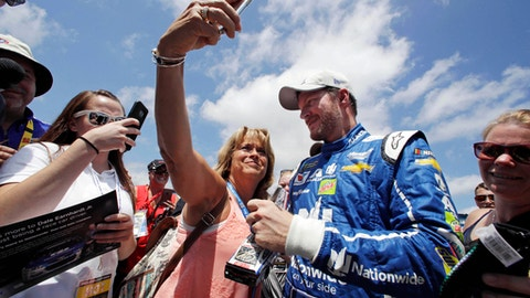 Mary Goodnow, of Londonderry, N.H., tries to snap a selfie with driver Dale Earnhardt Jr. while he signs autographs following a practice session for Sunday's Cup Series 301 auto race at the New Hampshire Motor Speedway in Loudon, N.H., Saturday, July 15, 2017. (AP Photo/Charles Krupa)