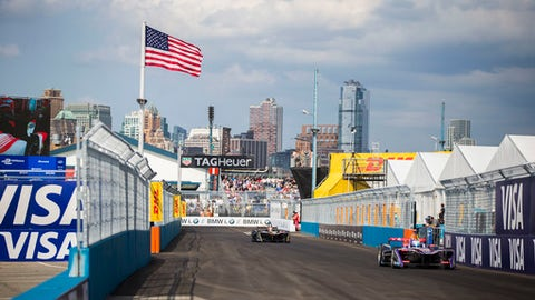 Sam Bird, right, drives during the Formula E all-electric New City ePrix Saturday, July 15, 2017, in the Brooklyn borough of New York. (AP Photo/Michael Noble Jr.)