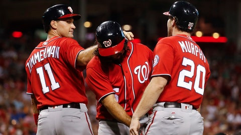 Washington Nationals' Anthony Rendon, center, celebrates with Ryan Zimmerman (11) and Daniel Murphy (20) after hitting a grand slam off Cincinnati Reds relief pitcher Blake Wood during the seventh inning of a baseball game, Saturday, July 15, 2017, in Cincinnati. (AP Photo/John Minchillo)